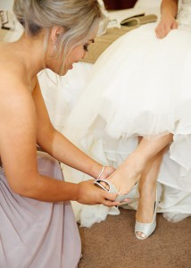 Bridesmaid putting on th bride's shoes