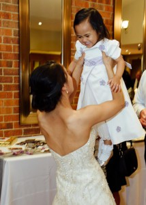 Bride lifting flower girl at reception
