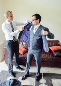 Groomsmen helping groom with jacket