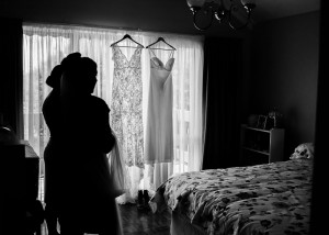 silhouette of bride and bridesmaid and dresses hanging in window