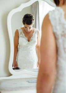 Bride looks down at dress in the mirror