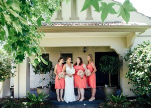 Bride and bridesmaids outside large house