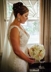 Bride looking down at bouquet, flowers