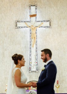 Bride and groom looking at each other, cross in background