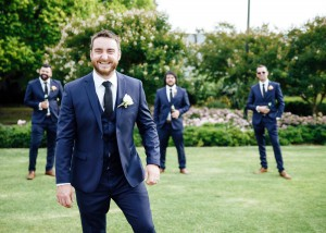 Groom with groomsmen in background