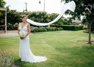 Bride in a garden with veil flying
