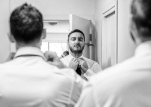 Groom adjusting tie in mirror
