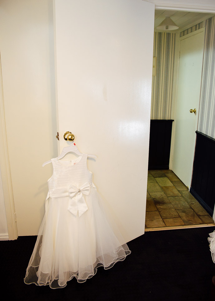 Flower girl dress hanging on a door