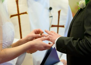 bride-placing-ring-on-grooms-finger